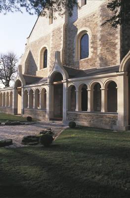 Fachada de la sala de enfermos del siglo XII Con contrafuertes que mezclan toba y esquisto de pizarra. La galería, vestigio de un antiguo claustro, data del  siglo XVII.