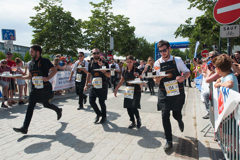 Chaud devant! Le départ est lancé pour la course des serveuses et garçons de café.
