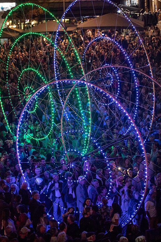 """Dix roues illuminées en déambulation avec danse et musique: """"Color Wheels""""."""