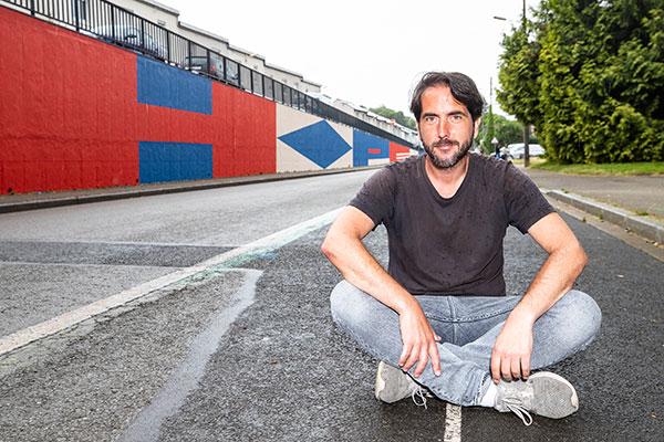 Portrait de Damien Poulain devant la fresque qu'il a réalisée.